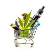 Small shopping cart filled with CBD products and cannabis leaf