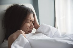 Woman with painful headache in bed