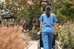 Rearview shot of a caregiver and her patient out for a walk in facility garden