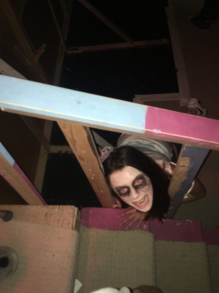 Drama Club member hides under stage staircase to scare groups walking through the house.