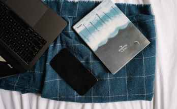 laptop cellphone and a notebook on blue blanket