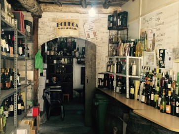 old taberna in Spain with bottles of wine and alcohol, barrels for tables