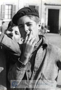 A boy with worn features and wrinkles under his eyes that do not belong on a teenager is posed smoking before the photographer.