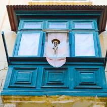Hellblauer Erker mit Klangspiel in Valletta