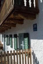 Fensterläsen und Holzbalkon eines Bauernhauses