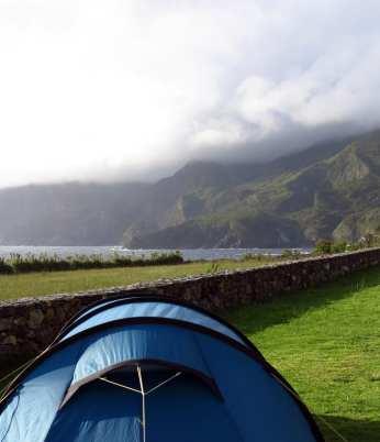 Zelt, dahinter Meer und Berge