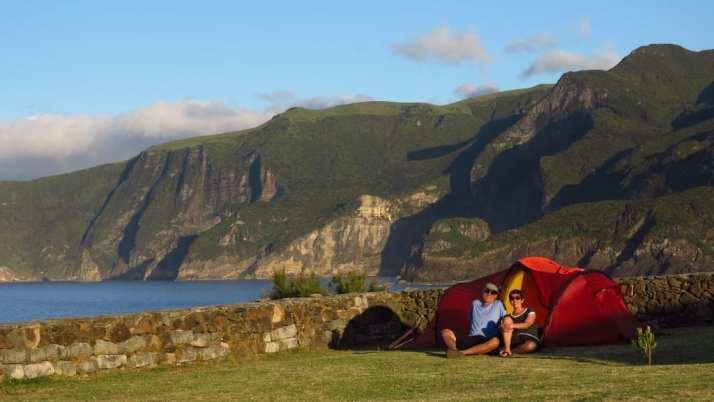 Paar sitzt vor Zelt, dahinter Meer und Berge
