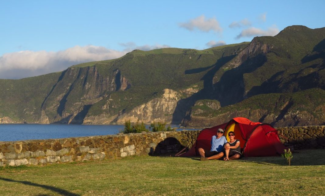 Paar sitzt vor Zelt, dahinter das Meer