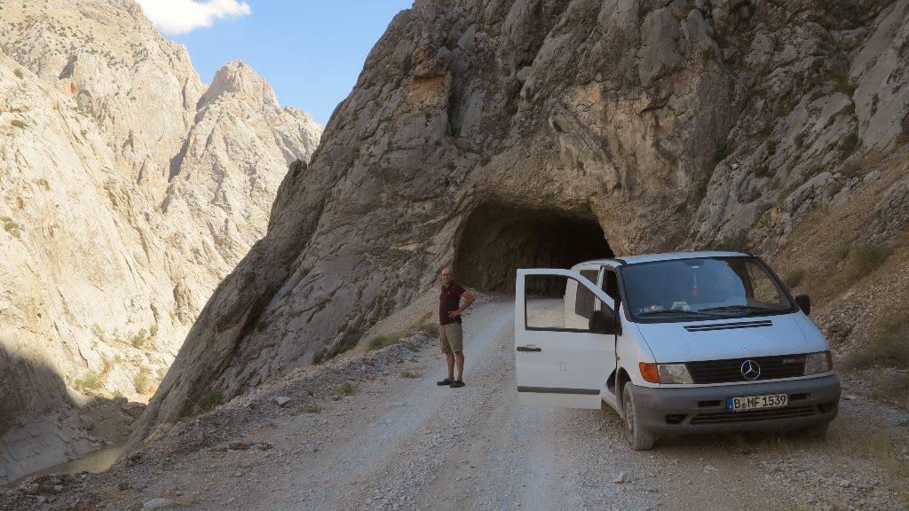 Bus auf Schotterstraße und Tunnel in Berglandschaft