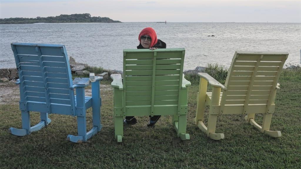Frau sitzt in Strandstühlen am Meer