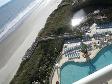 Blick von oben auf leeren Sandstrand und Pool