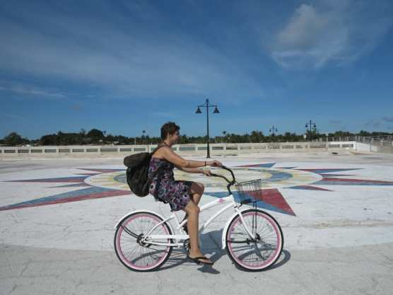 Frau fährt im Sommerkleid auf einem Fahrrad