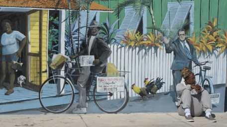 Mann sitzt vor Mural