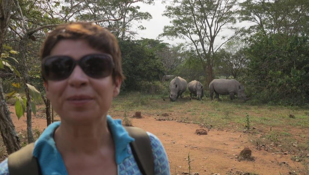 Frau steht vor grasenden Nashörnern