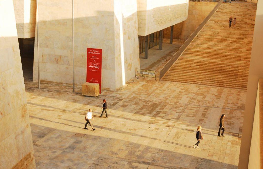 Menschen laufen zwischen moderner sandsteinfarbener Architektur herum