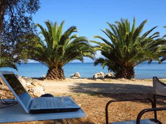Laptop vor Palme und Meer