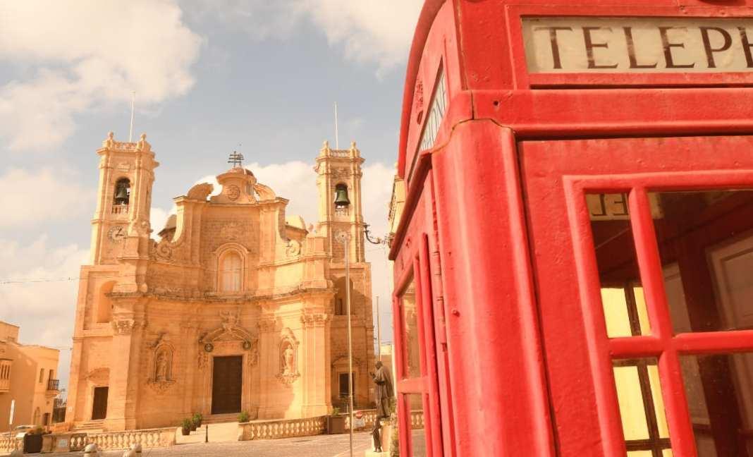 Rote Telefonzelle vor Kirche