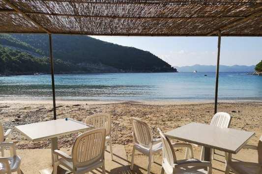 Plastikstühle unterm Dach an einem Strand