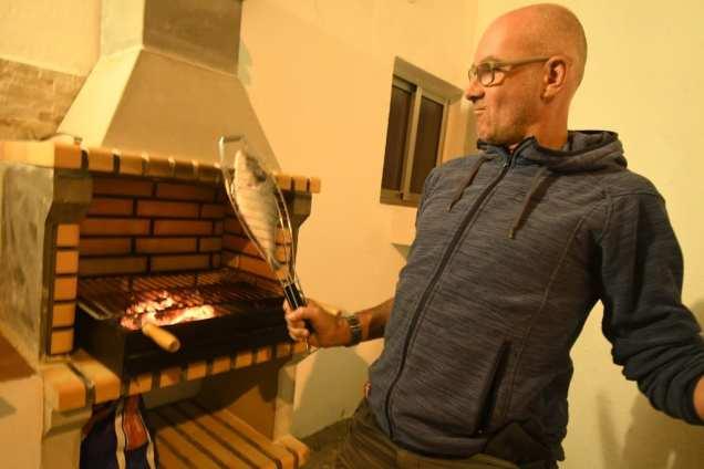 Mann grillt Fisch