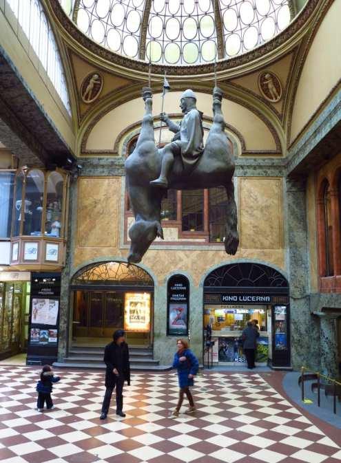 Skulptur Mann sitzt verkehrt auf einem Pferd