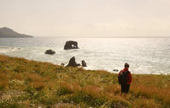 Wanderin mit roter Jacke auf einem Küstenwanderweg in Kreta