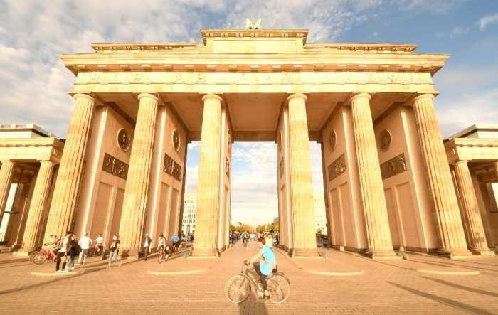 Frau radelt vor dem Brandenburger Tor