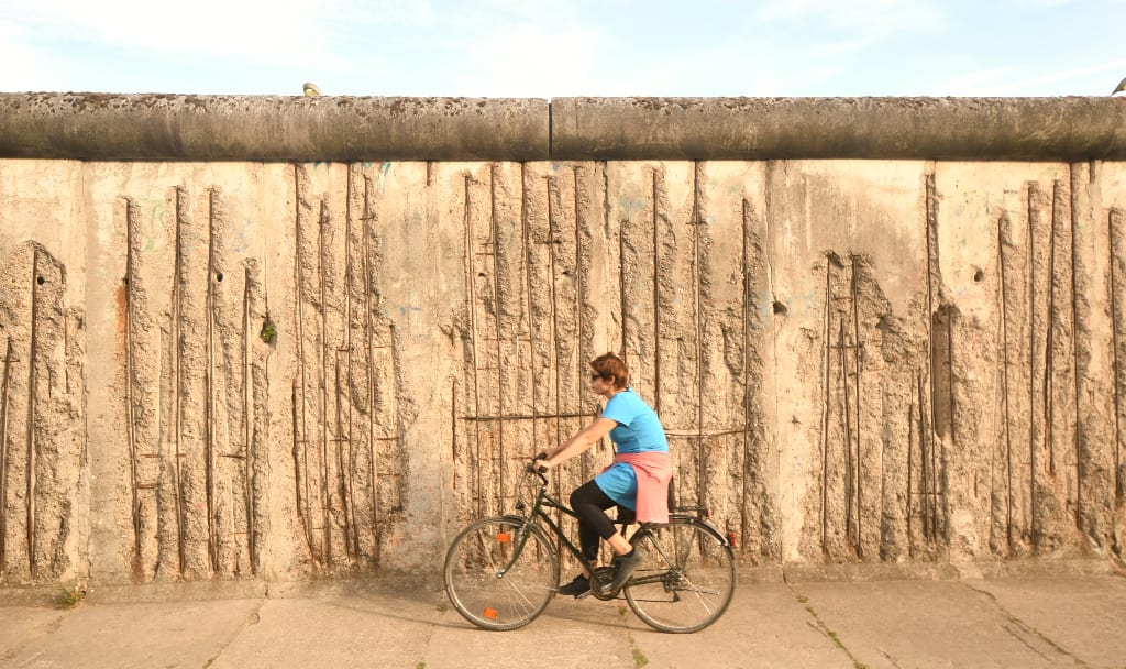 Frau fährt auf Fahrrad entlang der ehemaligen Berliner Mauer