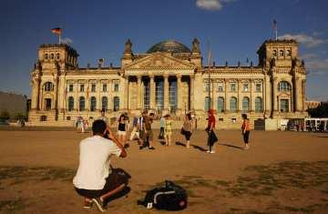 Mann fotografiert vor dem Reichstag in Berlin