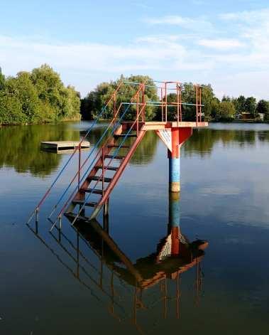 Badeteich mit Sprungbrett spiegelt sich im Wasser