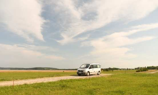 Grauer Minibus auf einem Schotterweg