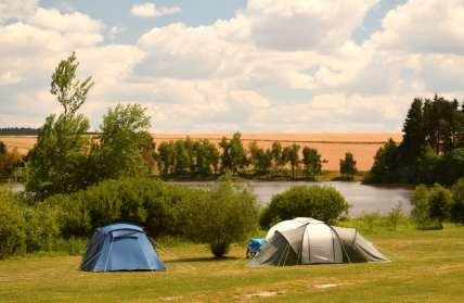 Zelte auf einer Wiese vor einem See