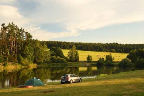 Auto und Zelt vor einem Teich