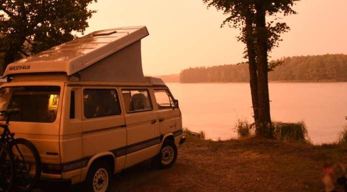 Camperbus an einem See im Abendlicht