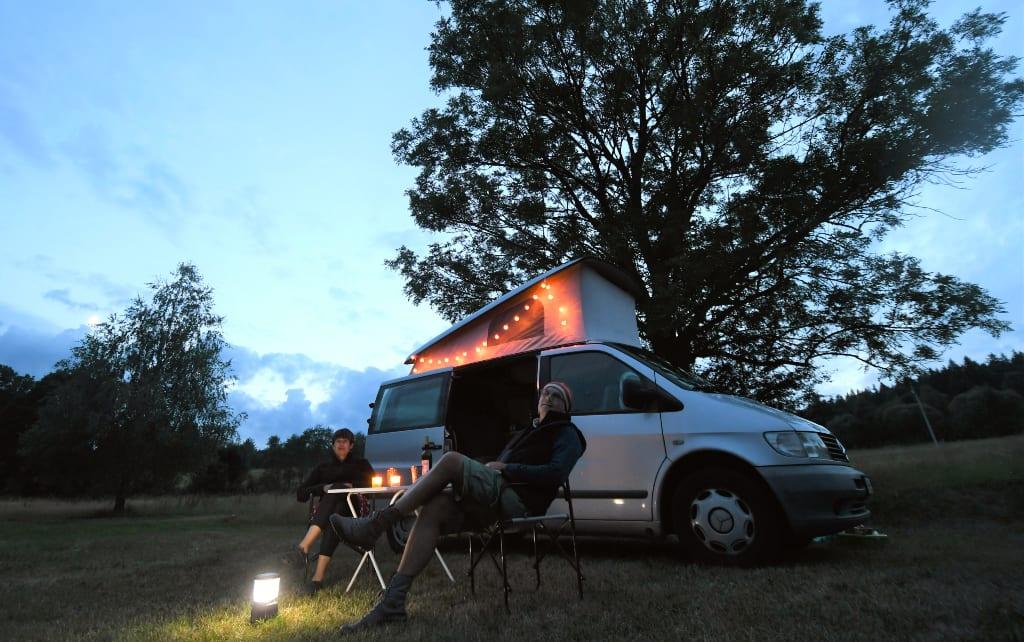 Zwei Personen sitzen vor ihrem Camperbus im Abendlicht
