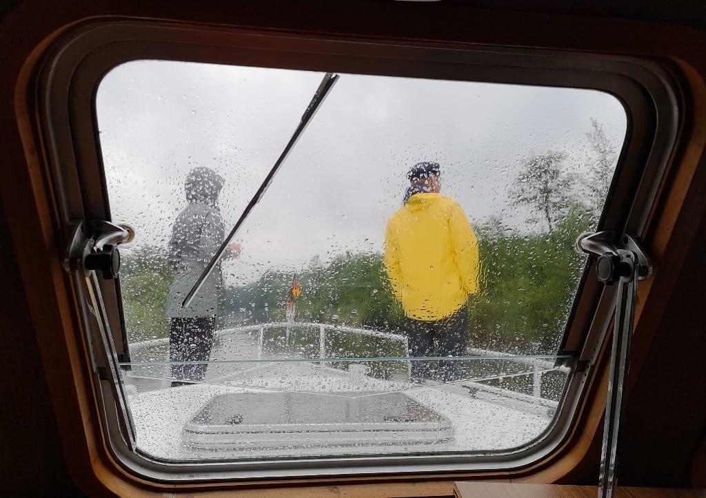 Zwei Personen mit Regenkleidung auf einem Boot