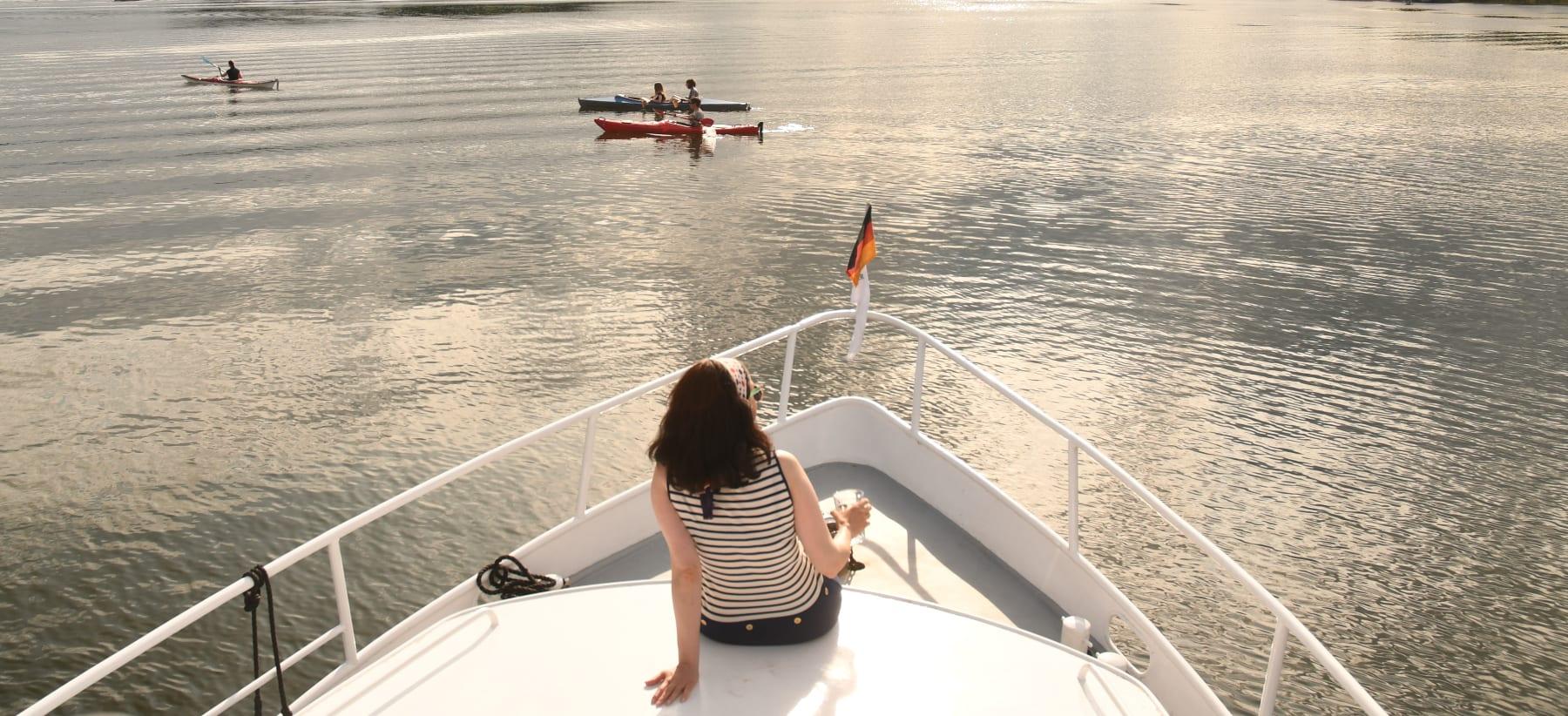 Frau sitzt auf Motorboot und schaut auf See