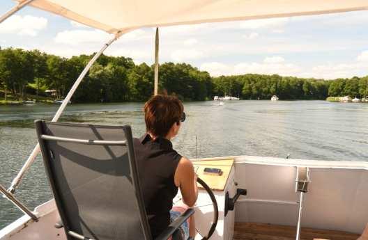 Frau steuert eine Motoryacht auf einem See