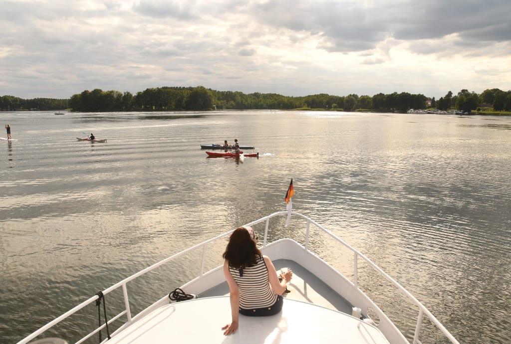 Frau sitzt auf Boot und schaut auf einen See
