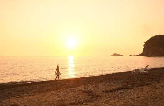 Frau läuft im Sonnenuntergang an einem Strand