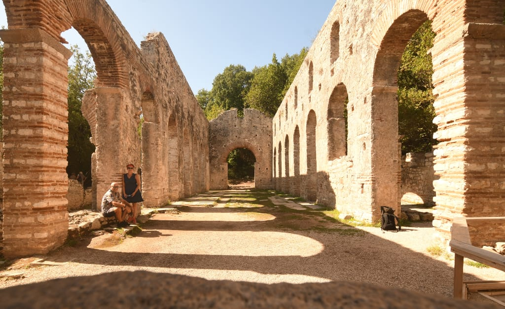 Zwei Menschen stehen in einer antiken Ruine
