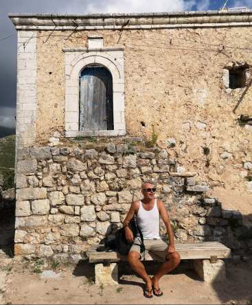 Mann sitzt vor Häuserruine