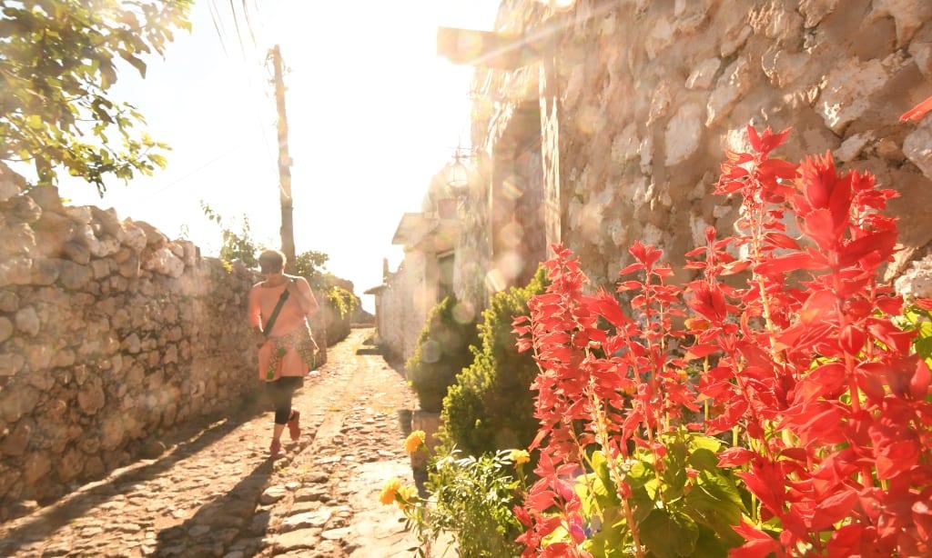 Frau läuft auf gepflasterten Weg, davor Blumen