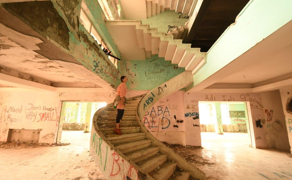 Frau auf einer Treppe in einer Häuserruine