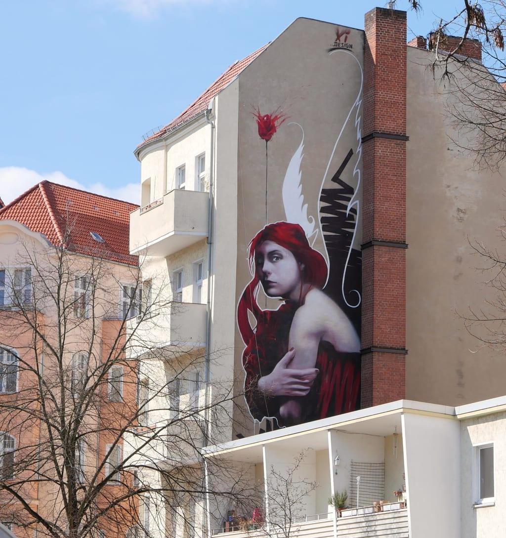 Mural einer Frau mit roten Haaren und Blume an Häuserwand