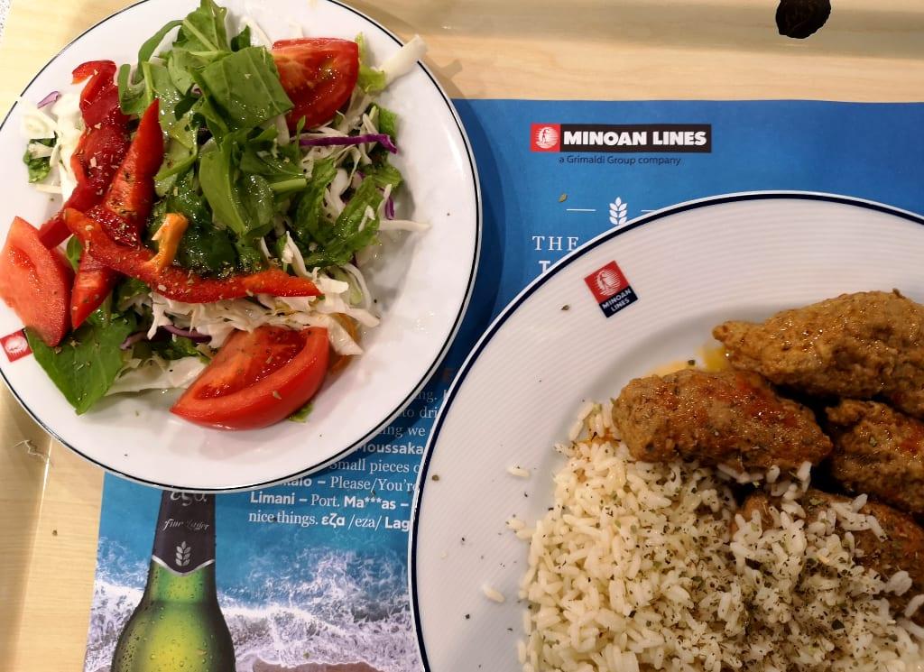 Zwei volle Teller mit Salat und Reis auf dem Plastiktablett einer Fährgesellschaft