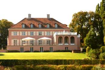 Rosafarbene Villa mit grünem Rasen davor