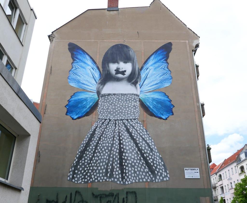Riesiges Mural mit einem Mädchen mit blauen Schmetterlingsflügeln