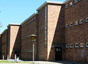 Backsteingebäude mit kleinen Fenstern und Laterne davor