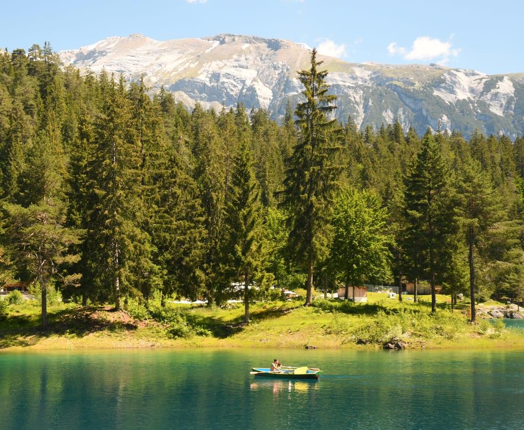 Boot auf einem grün leuchtenden See, dahinter Berge