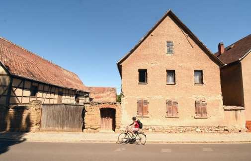 Braunes Dorf mit Radlerin